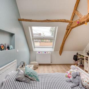 Réalisation d'une chambre d'enfant minimaliste avec un mur blanc, un sol en bois clair et un sol beige.