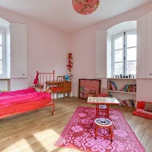 Foto di una grande cameretta per bambini da 4 a 10 anni bohémian con pareti rosa e pavimento in legno massello medio