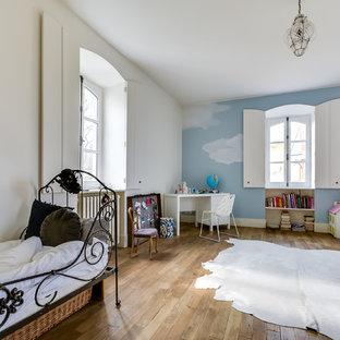 Inspiration pour une grand chambre d'enfant de 4 à 10 ans traditionnelle avec un mur bleu et un sol en bois brun.