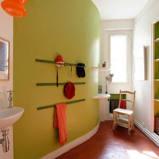Idée de décoration pour une petite chambre neutre de 4 à 10 ans design avec un bureau, un mur vert, un sol en carreau de terre cuite et un sol rouge.