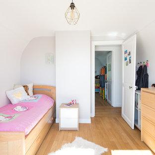 Idées déco pour une chambre d'enfant de 4 à 10 ans contemporaine avec un mur blanc, un sol en bois clair et un sol beige.