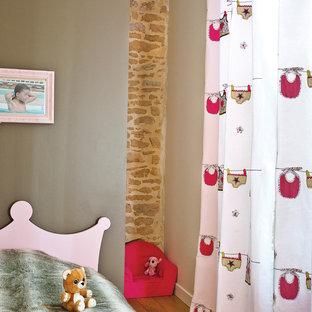 Idées déco pour une chambre d'enfant de 4 à 10 ans contemporaine de taille moyenne avec un sol en bois brun et un mur multicolore.