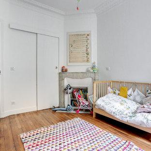 Aménagement d'une chambre d'enfant de 1 à 3 ans scandinave avec un mur blanc, un sol en bois brun et un sol marron.