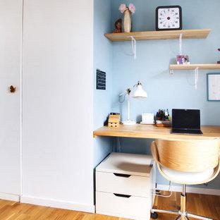 Cette image montre une chambre de garçon design de taille moyenne avec un bureau, un mur bleu, un sol en bois clair, un sol marron et du papier peint.