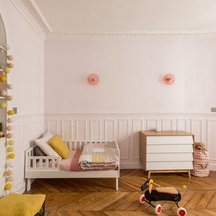 Cette image montre une chambre d'enfant design avec un mur rose et un sol en bois brun.