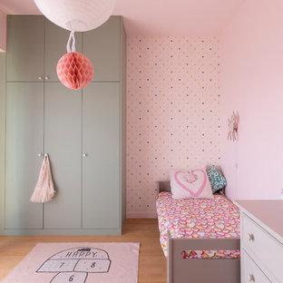 Exemple d'une chambre d'enfant de 4 à 10 ans tendance avec un mur rose, un sol en bois clair et un sol beige.