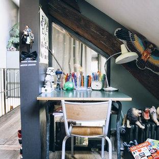 Réalisation d'une chambre neutre de 4 à 10 ans design de taille moyenne avec un bureau, un mur multicolore et un sol en bois clair.