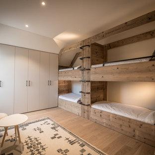 Inspiration för ett mellanstort rustikt könsneutralt barnrum kombinerat med sovrum och för 4-10-åringar, med beige väggar och ljust trägolv