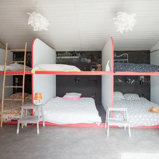 Bild på ett mellanstort funkis könsneutralt barnrum kombinerat med sovrum och för 4-10-åringar, med betonggolv och flerfärgade väggar