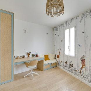 Esempio di una grande cameretta per bambini da 4 a 10 anni moderna con pareti bianche, pavimento in legno massello medio, pavimento beige e carta da parati