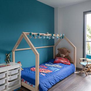 Idée de décoration pour une chambre d'enfant de 4 à 10 ans design avec un mur blanc, un sol en bois foncé et un sol marron.