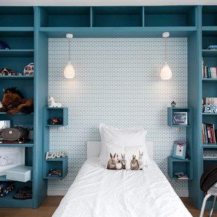 Réalisation d'une grande chambre d'enfant design avec un mur bleu, sol en stratifié et un sol beige.
