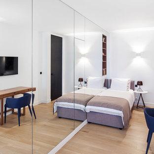 Cette image montre une chambre d'enfant minimaliste de taille moyenne avec un mur blanc, un sol en bois clair et un sol beige.