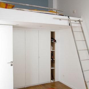 Cette image montre une chambre d'enfant urbaine de taille moyenne avec un sol en bois brun et un mur multicolore.