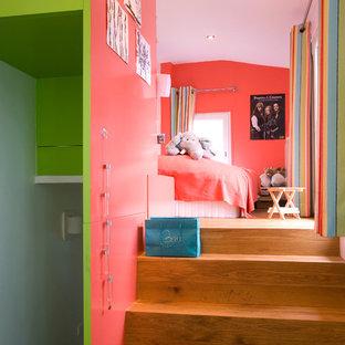 Cette photo montre une grande chambre d'enfant de 4 à 10 ans tendance avec un mur rose et un sol en bois brun.