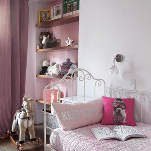 Idée de décoration pour une chambre d'enfant de 4 à 10 ans design de taille moyenne avec un sol en bois brun et un mur multicolore.