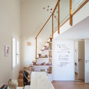 Exemple d'une grand chambre de fille de 4 à 10 ans tendance avec un bureau, un mur blanc et un sol en bois foncé.