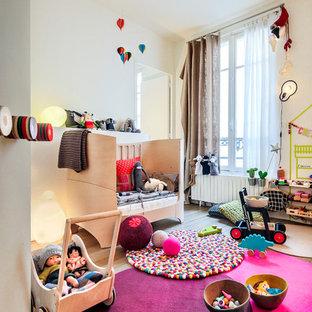 Réalisation d'une chambre d'enfant de 1 à 3 ans design de taille moyenne avec un mur blanc et un sol en bois brun.