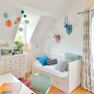 Inspiration pour une chambre de fille nordique avec un bureau, un mur blanc et un sol en bois brun.