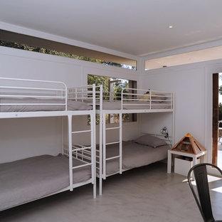 Exemple d'une grand chambre d'enfant de 4 à 10 ans tendance avec un mur blanc et béton au sol.