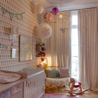 Imagen de habitación de bebé niña nórdica con paredes multicolor, suelo de madera clara y suelo beige