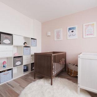 Cette image montre une chambre de bébé fille nordique avec un mur rose et un sol beige.
