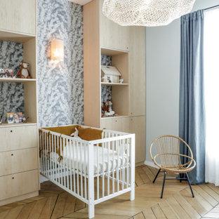 Cette image montre une chambre de bébé neutre nordique avec un mur gris, un sol en bois brun, un sol marron et du papier peint.