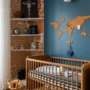 Inspiration pour une chambre de bébé nordique avec un mur bleu, un sol en bois brun et un mur en parement de brique.
