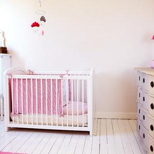 Cette image montre une chambre de bébé fille traditionnelle de taille moyenne avec un mur blanc et un sol en bois peint.