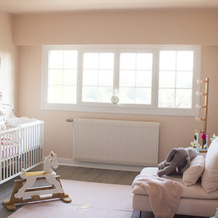 Inspiration for a mid-sized shabby-chic style girl laminate floor and gray floor nursery remodel in Other with pink walls