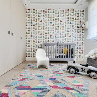 Aménagement d'une chambre de bébé neutre scandinave avec un mur beige, un sol en bois clair et un sol beige.