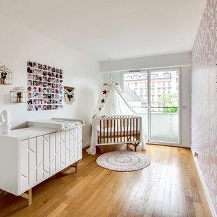Inspiration pour une petit chambre de bébé fille design avec un mur rose, un sol en bois brun et un sol marron.