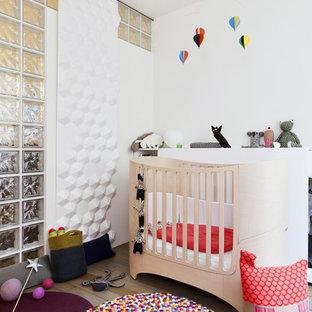 Inspiration pour une chambre de bébé neutre design de taille moyenne avec un mur blanc et un sol en bois clair.