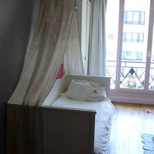 Inspiration for a large eclectic nursery for girls in Paris with beige walls, light hardwood flooring and beige floors.