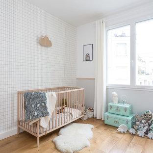 Idées déco pour une chambre de bébé neutre scandinave de taille moyenne avec un mur multicolore, un sol en bois brun et un sol beige.
