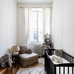 Exemple d'une chambre de bébé chic avec un mur blanc, un sol en bois brun et un sol marron.