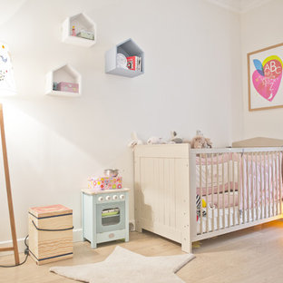 Idées déco pour une chambre de bébé neutre contemporaine de taille moyenne avec un mur blanc, un sol en bois clair et un sol beige.