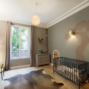 Modelo de habitación de bebé niño actual, de tamaño medio, con suelo de madera clara, paredes marrones y suelo marrón
