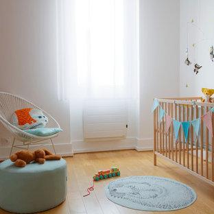 Inspiration pour une chambre de bébé neutre nordique avec un mur blanc, un sol en bois clair et un sol beige.