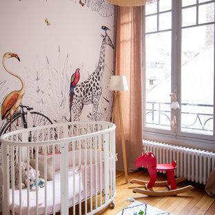 Inspiration pour une chambre de bébé fille design de taille moyenne avec un mur beige, un sol en bois clair, un sol marron et du papier peint.