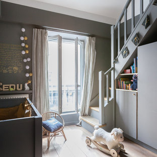 Photo of a medium sized contemporary gender neutral nursery in Paris with grey walls, light hardwood flooring and beige floors.