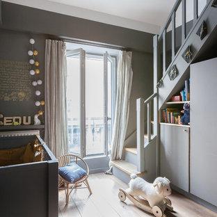 Exemple d'une chambre de bébé neutre tendance de taille moyenne avec un mur gris, un sol en bois clair et un sol beige.