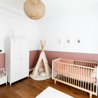 Mid-sized contemporary nursery in Paris with pink walls, dark hardwood floors and brown floor for girls.