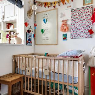 Cette image montre une petit chambre de bébé neutre bohème avec un mur blanc.
