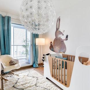 Cette image montre une chambre de bébé neutre design de taille moyenne avec un mur blanc et un sol en bois clair.