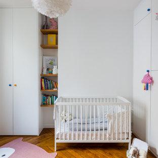 Exemple d'une chambre de bébé fille tendance avec un mur blanc, un sol en bois brun et un sol marron.