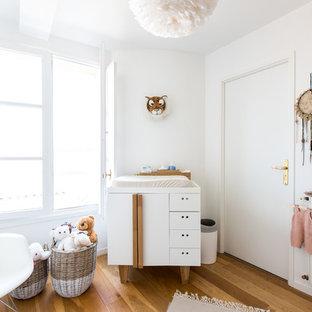 Aménagement d'une chambre de bébé fille scandinave avec un mur blanc, un sol en bois brun et un sol marron.