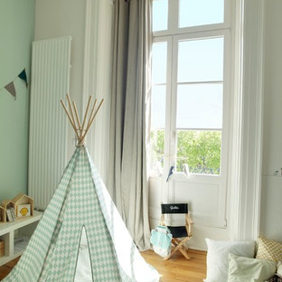 This is an example of a medium sized scandi nursery for boys in Dijon with white walls and medium hardwood flooring.