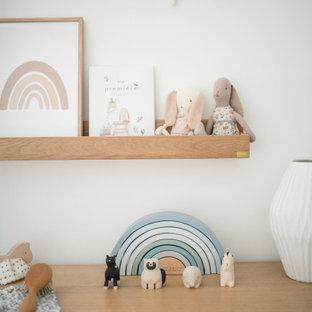 Réalisation d'une petit chambre de bébé fille champêtre avec un mur bleu, un sol en bois clair, un sol beige, un plafond en lambris de bois et du papier peint.