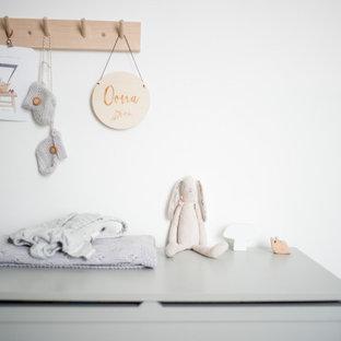 Foto de habitación de bebé niña papel pintado, de estilo de casa de campo, pequeña, con paredes azules, suelo de madera clara, suelo beige y papel pintado